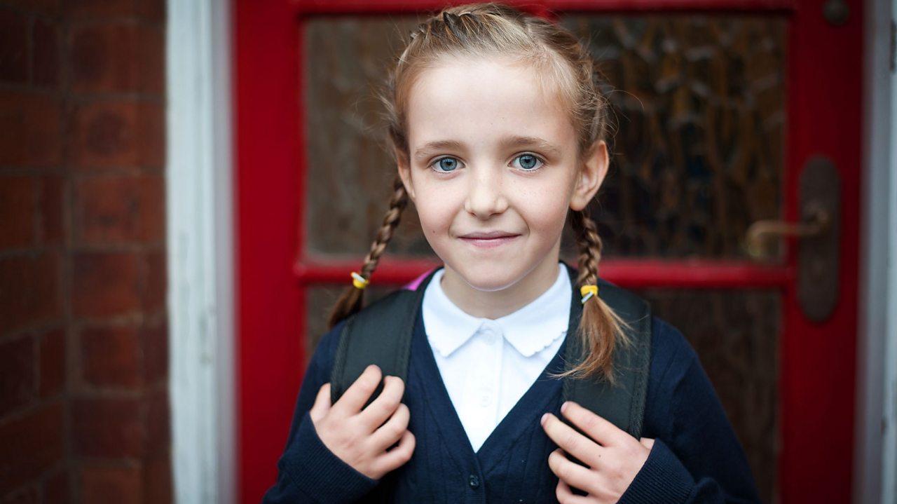 A school girl stood in front of a door.