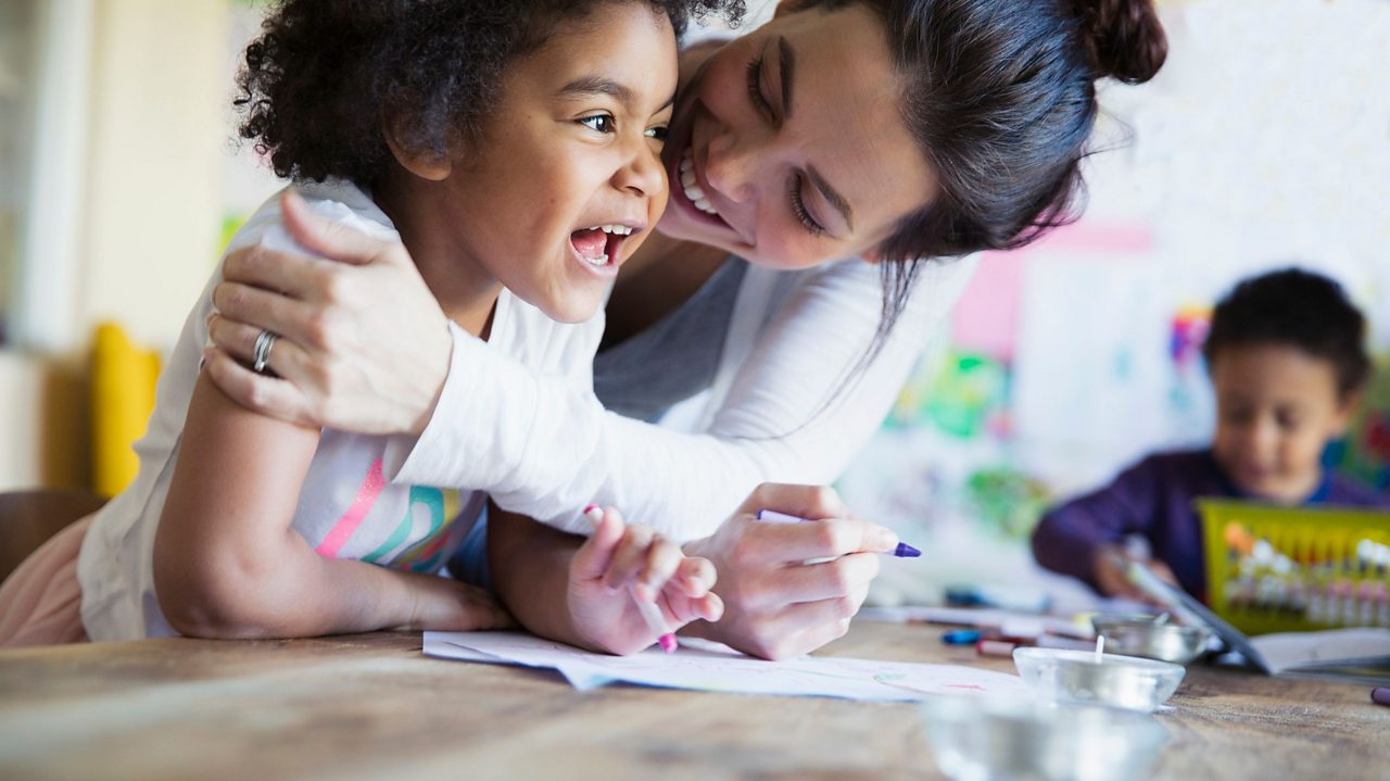 A mother and daughter laughing and drawing.
