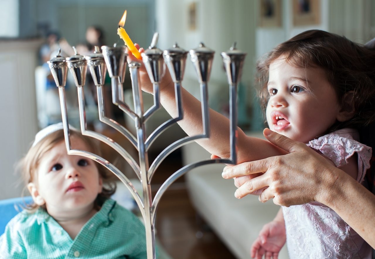 Two young children light candles on a menorah.