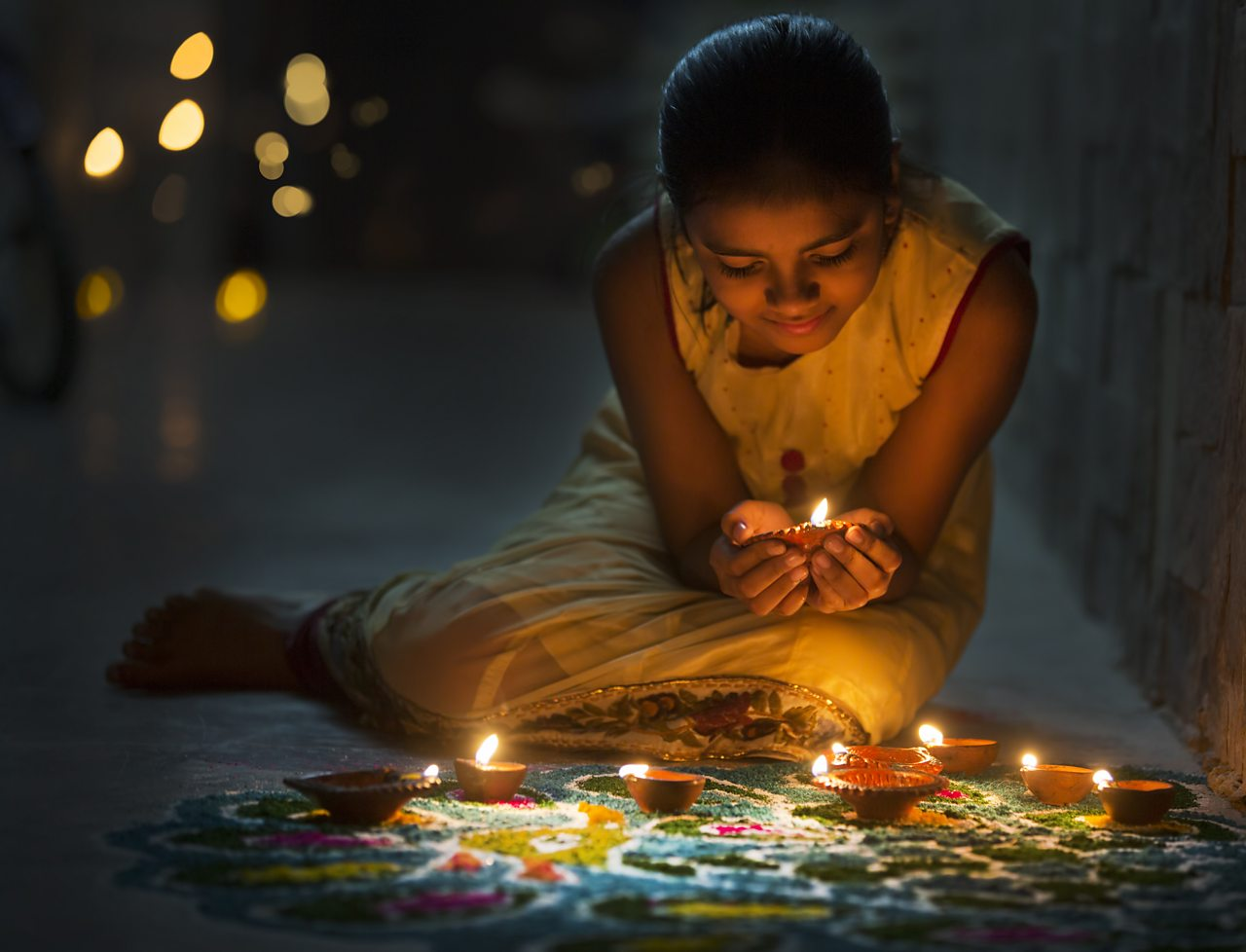 Young girl celebrating Diwali.  She is surrounded by candles and is holding one in cupped hands.