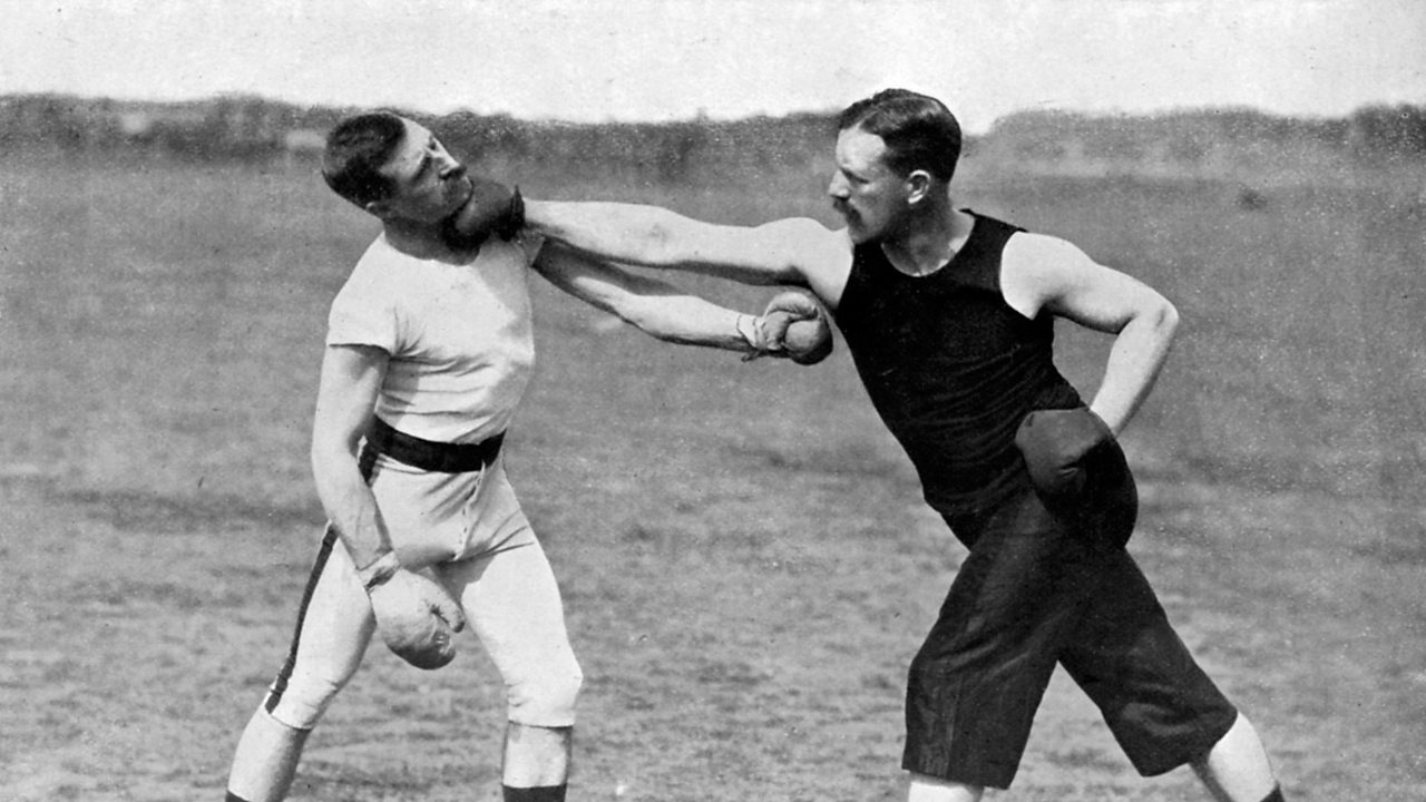 Two fighters demonstrate a boxing move.