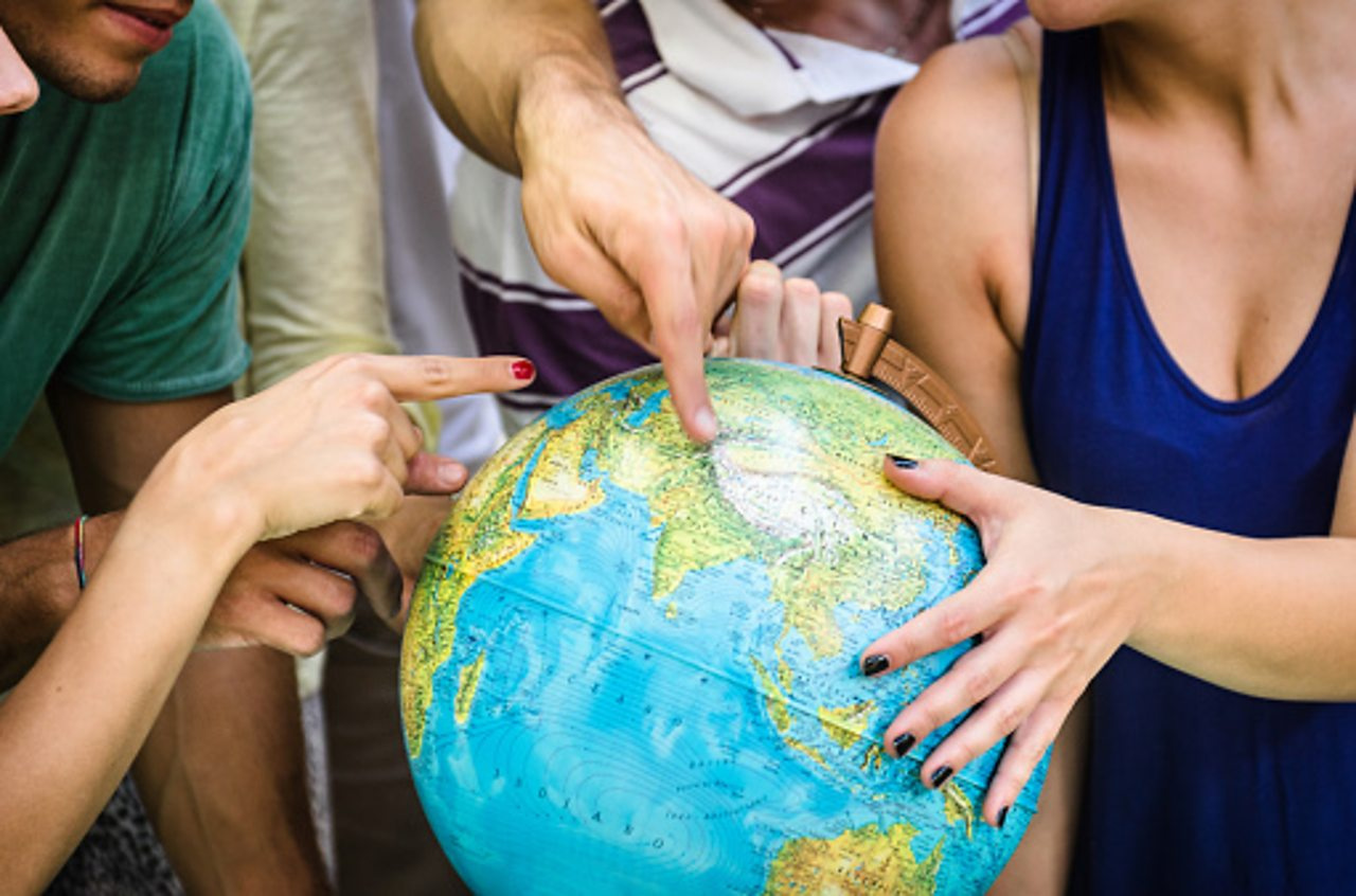 Students pointing at different countries on a globe.