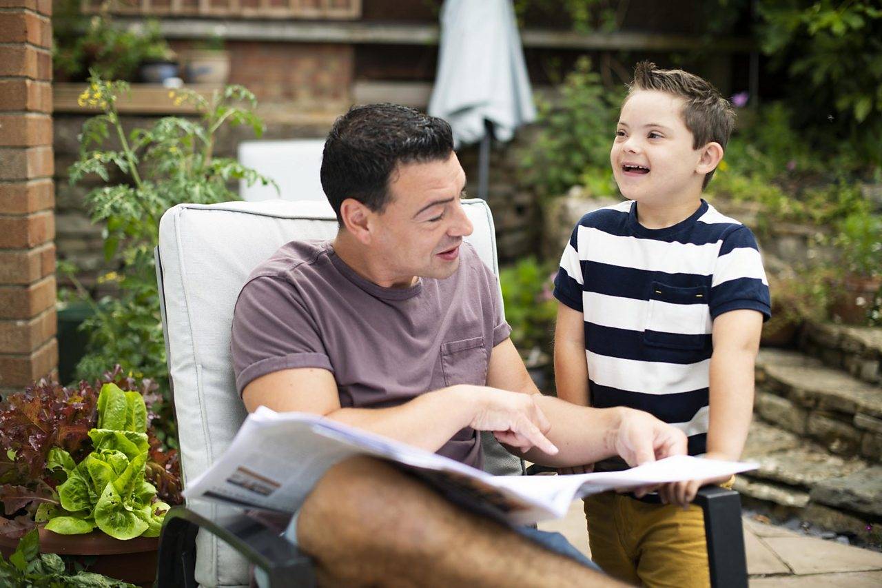 Dad and son in a garden looking at a newspaper