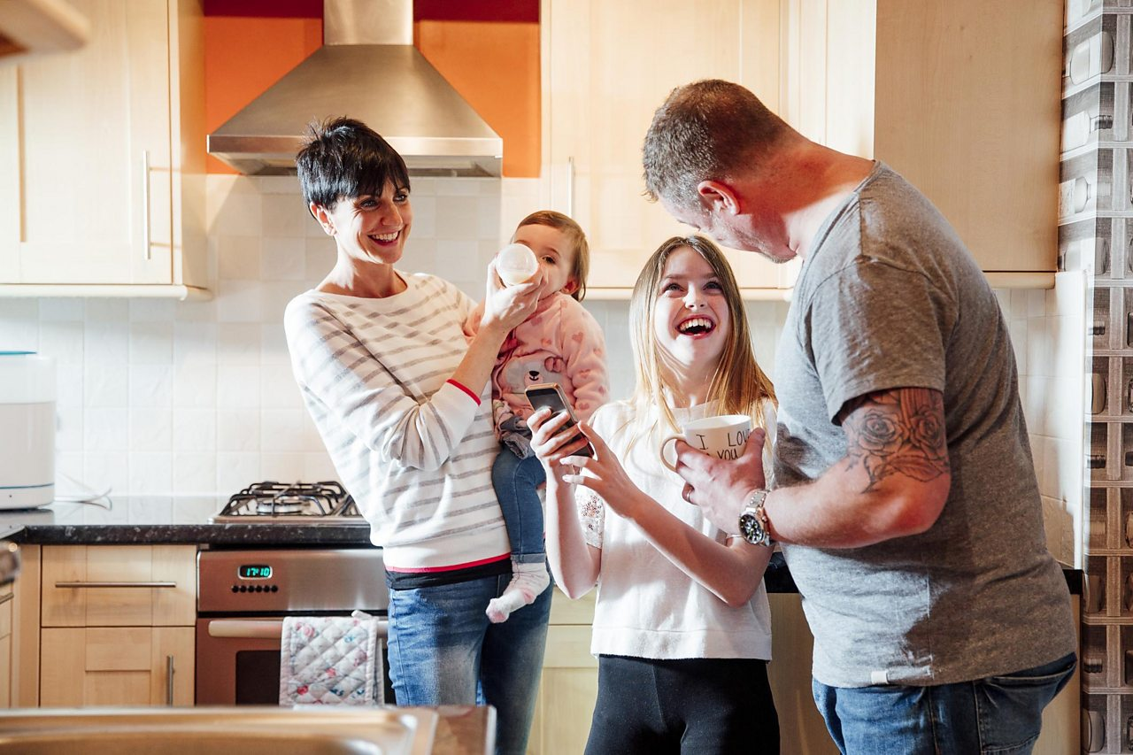 A mum and dad in a kitchen with two children