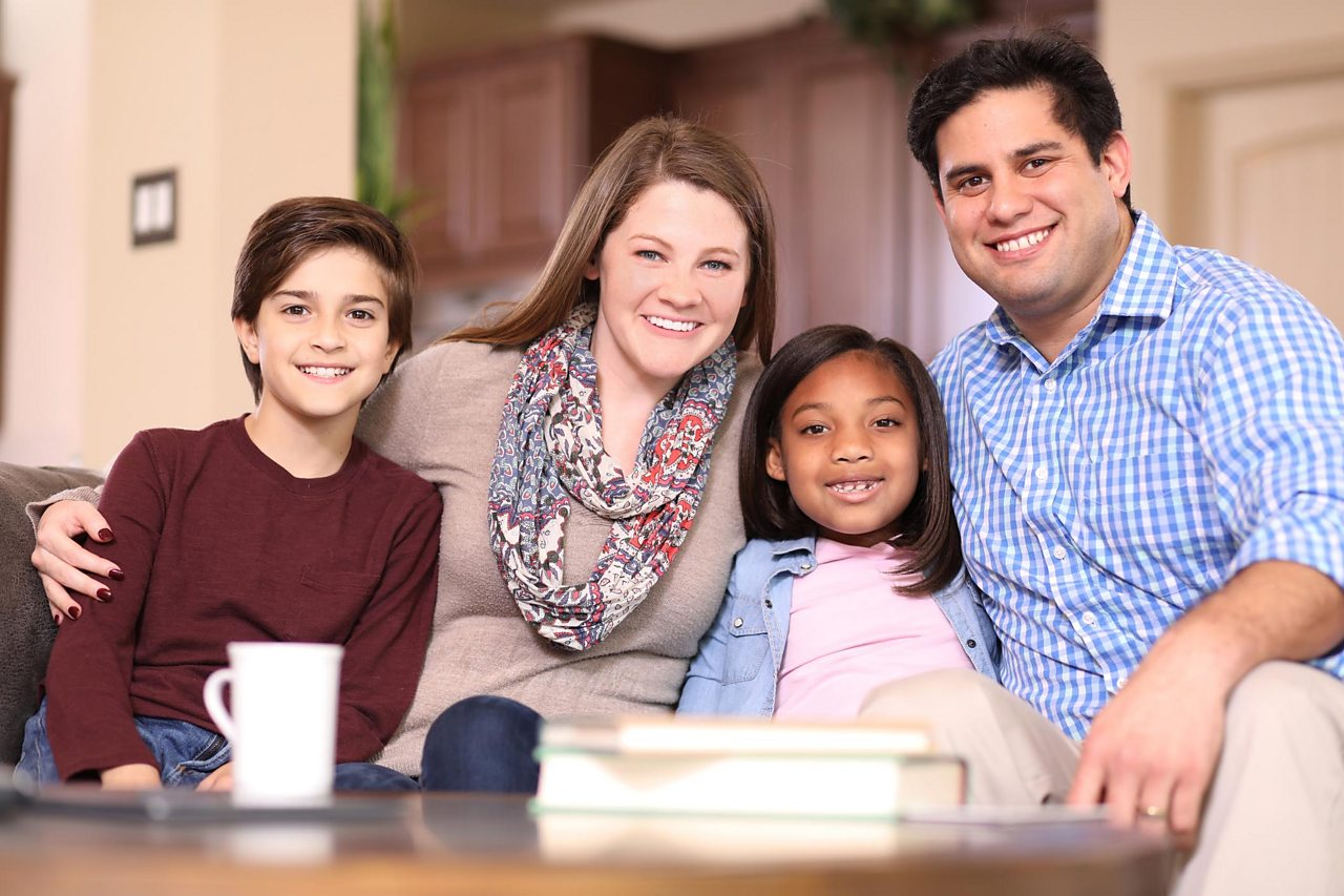 A foster family sitting in a living room