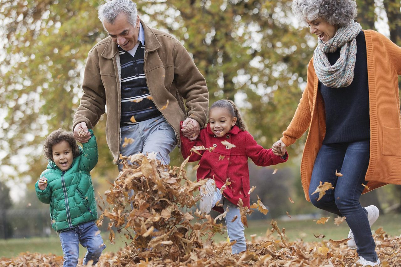 Grandparents kicking autumn leaves with two grandchildren
