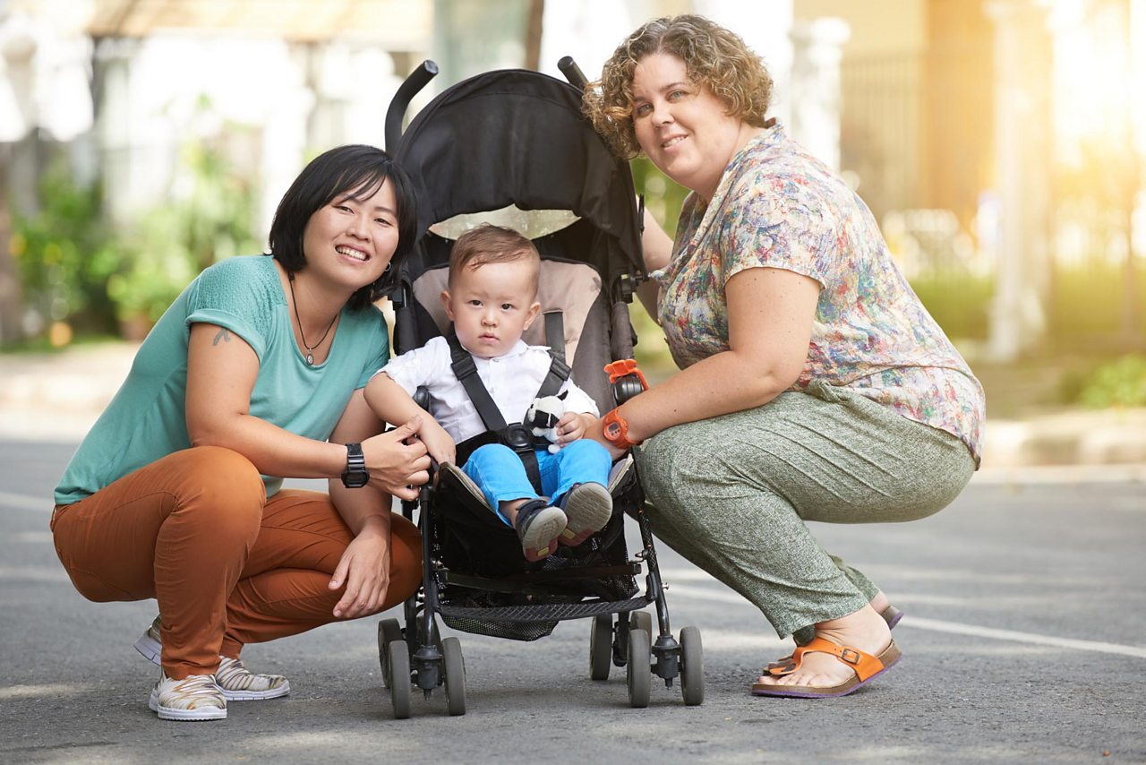 A child in a pushchair with two mums