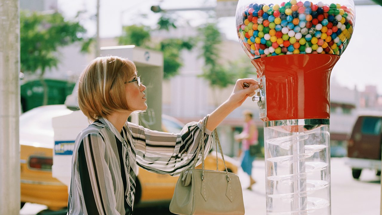 A woman using a gumball machine.