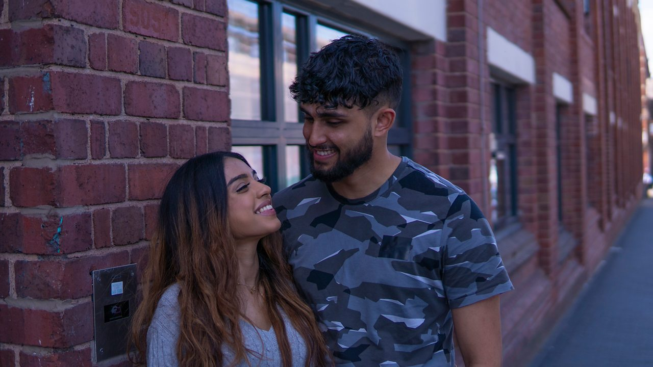 Tanya and Ryhan smiling at each other outside their property