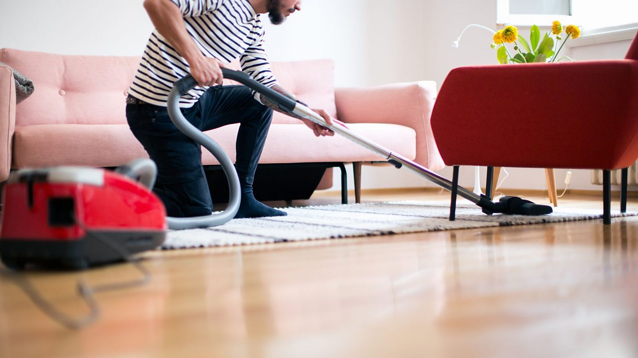 A man using a vacuum cleaner on the floor.
