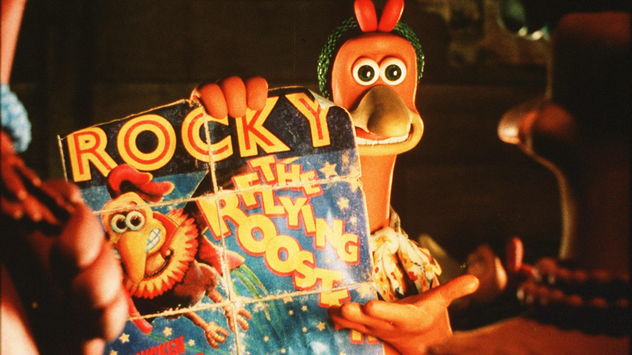 """Ginger holding a poster showing Rocky """"flying""""."""