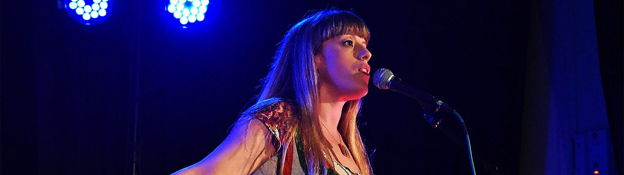 Somerset poet Liv Torc on stage in front of a microphone