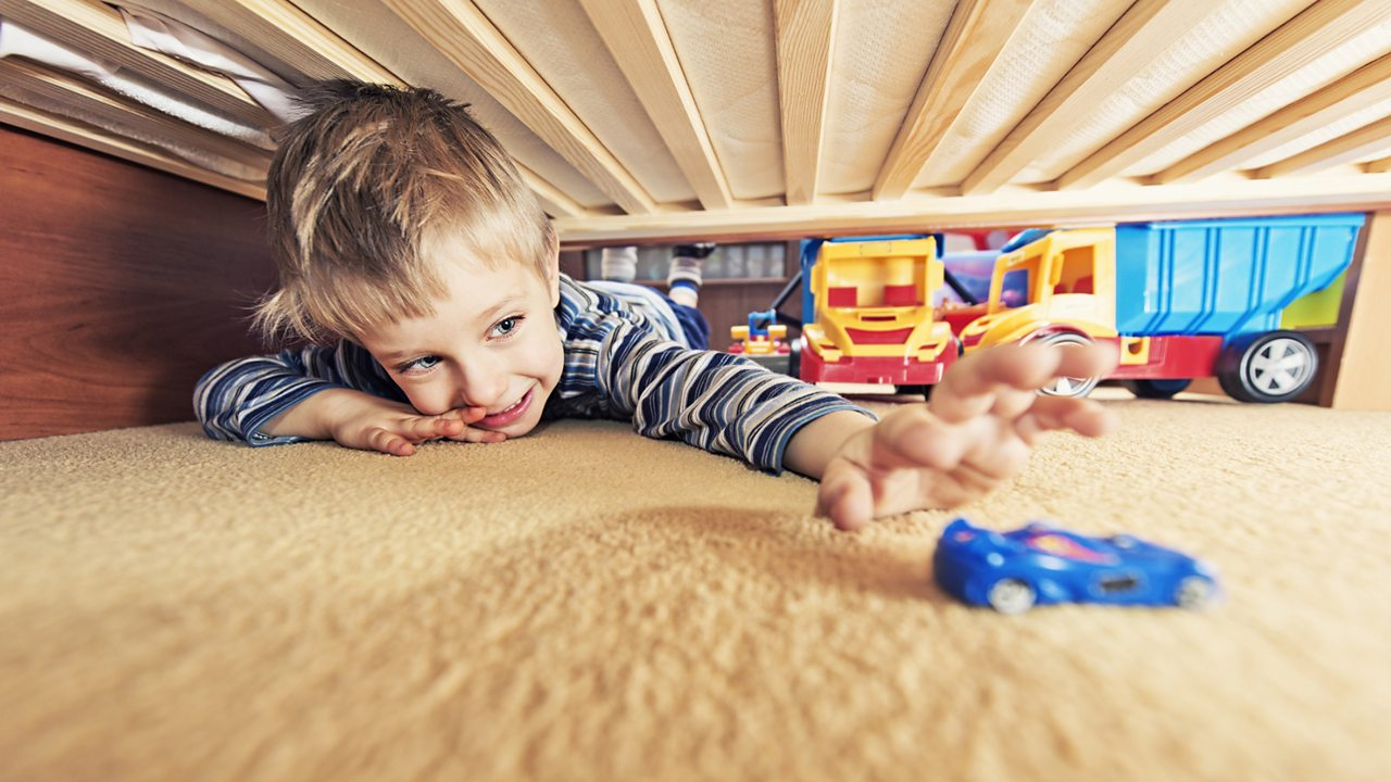 Boy reaching for a toy car