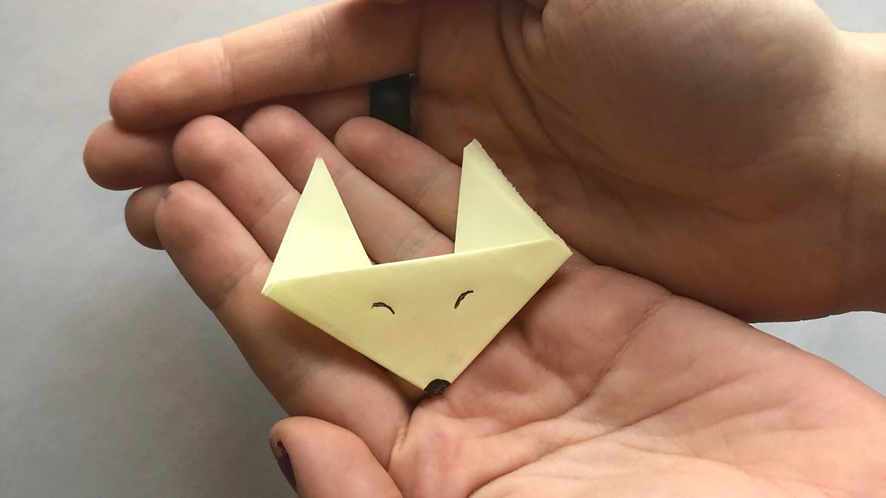 A yellow origami fox face in a pair of hands.