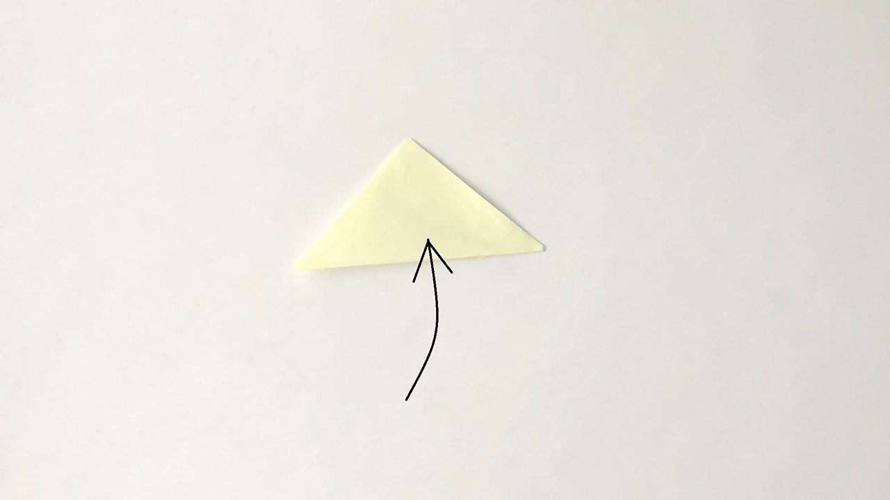 The square of paper is now folded in half to make a triangle.