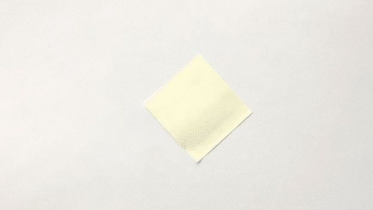 A yellow square of paper on a white background.