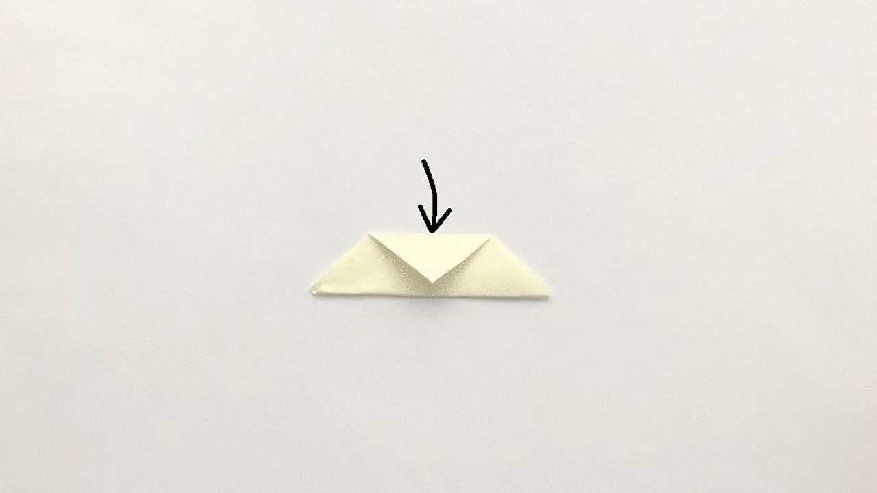 The top of the triangle is folded down towards its longest edge.