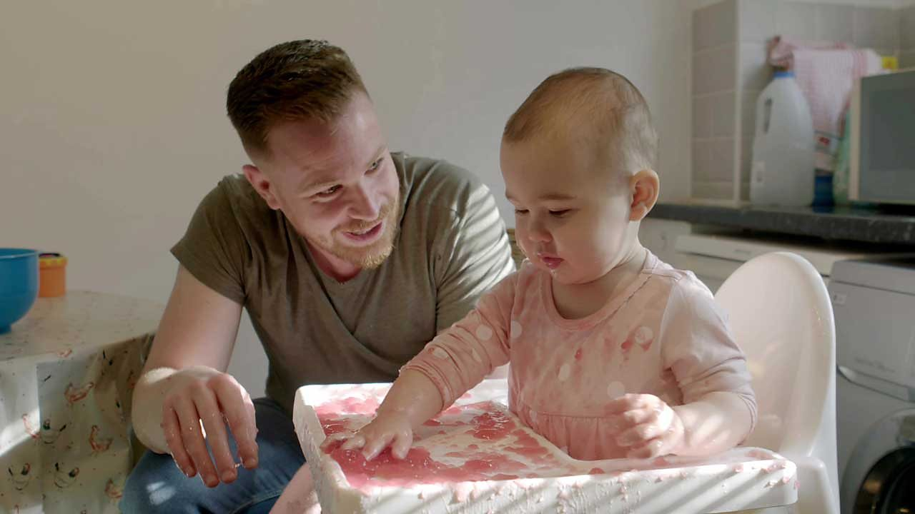 A dad and his daughter playing with jelly.