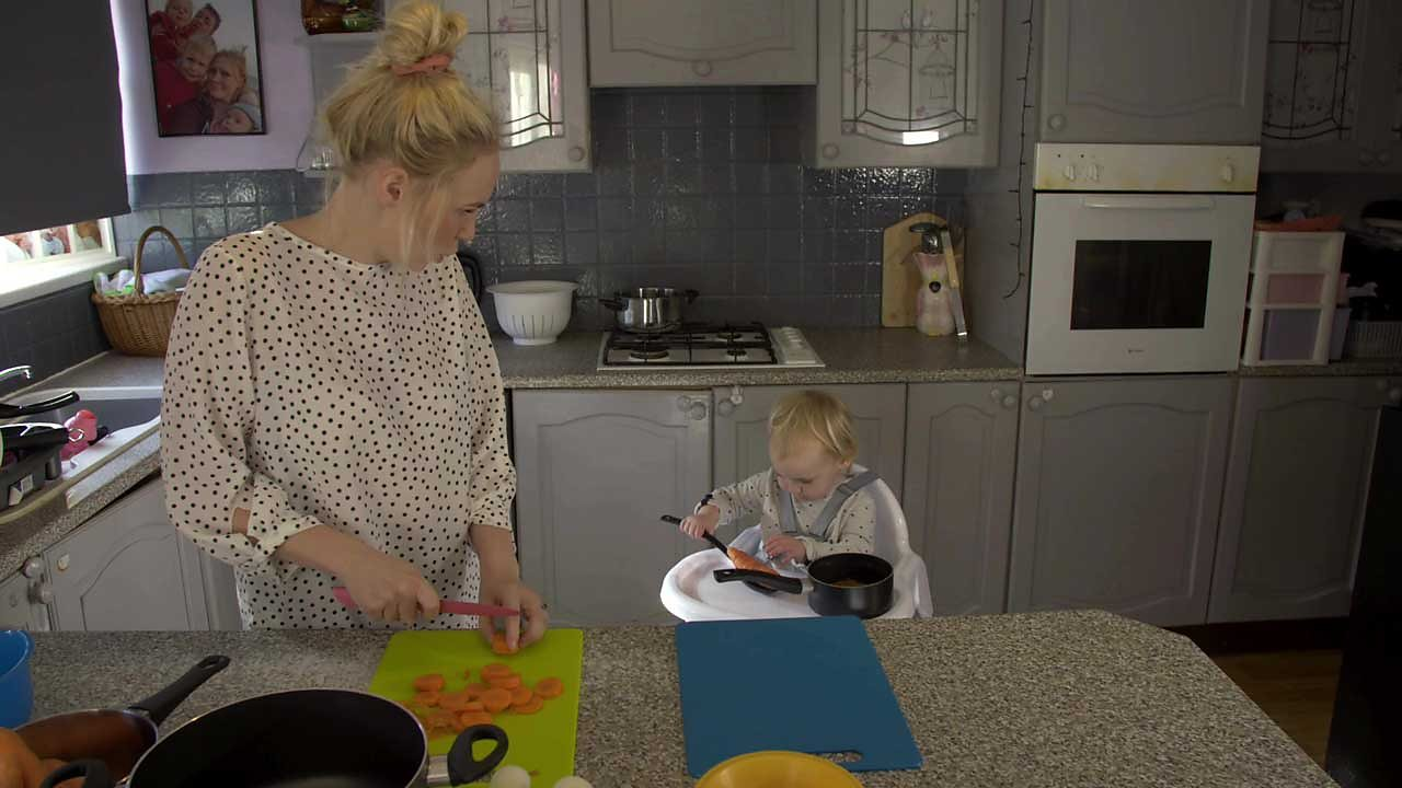 A mum chopping carrots and looking on at her daughter in a high chair playing with vegetables.