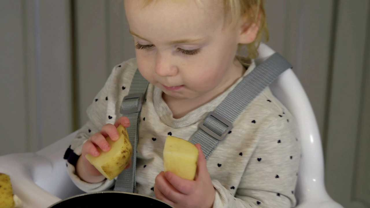 A little girl holding two chunks of potato.