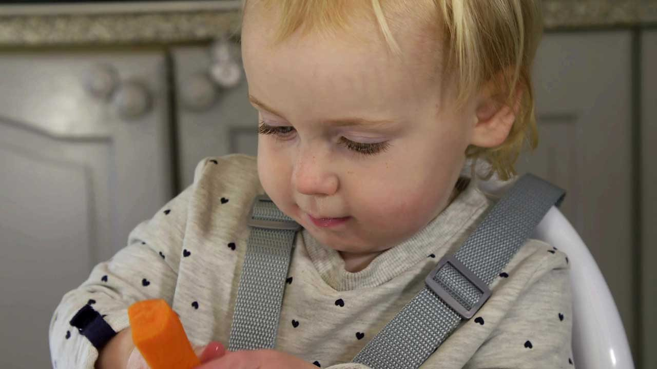 A little girl looking at a carrot.