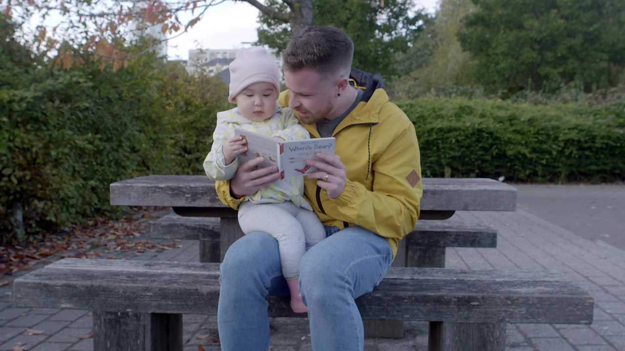 A dad and his little girl reading a book on a bench.