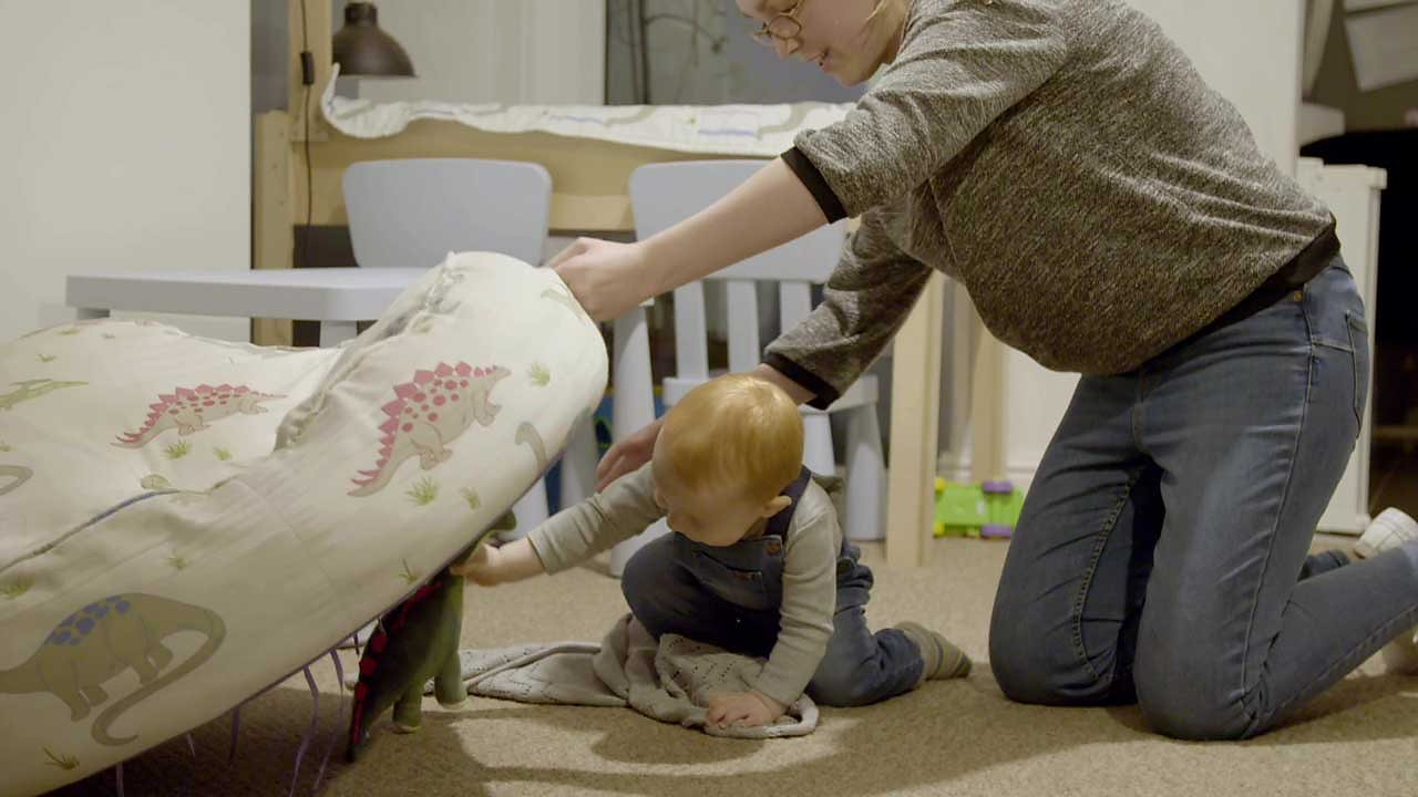 A mum and her son hiding a toy dinosaur.