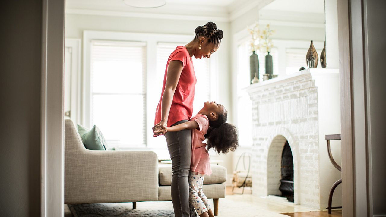 A mother looks down at her daughter who stands on her feet