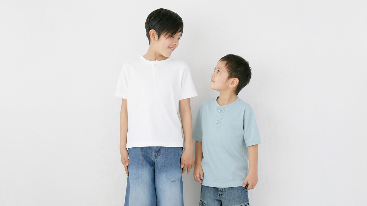 Two brothers stand side by side comparing their height