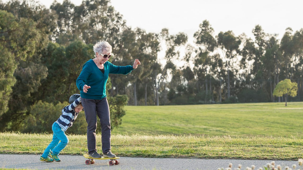 A grandmother plays on a skateboard with her grandchild who is helping her