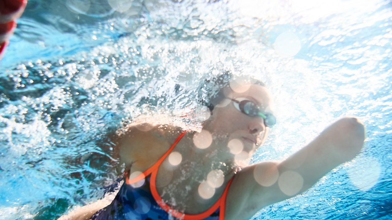 An underwater image of a woman swimming in a pool