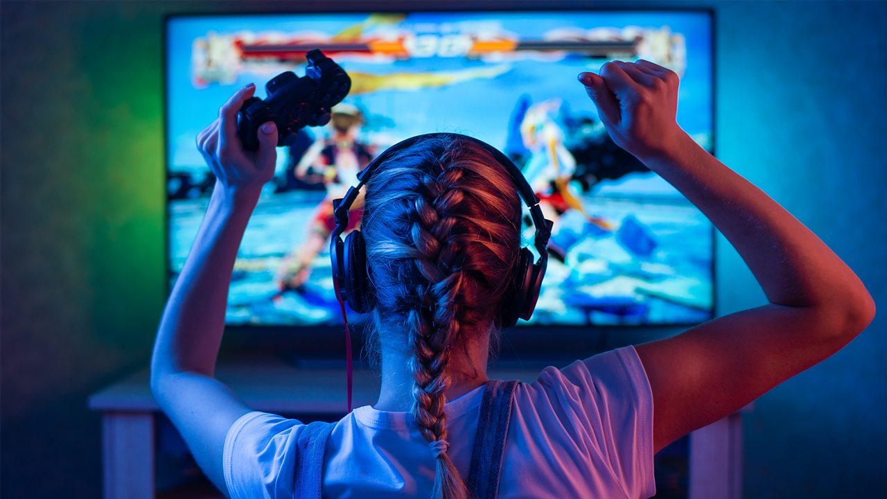 A person cheers with a game controller in their hand as they play a fighting video game.