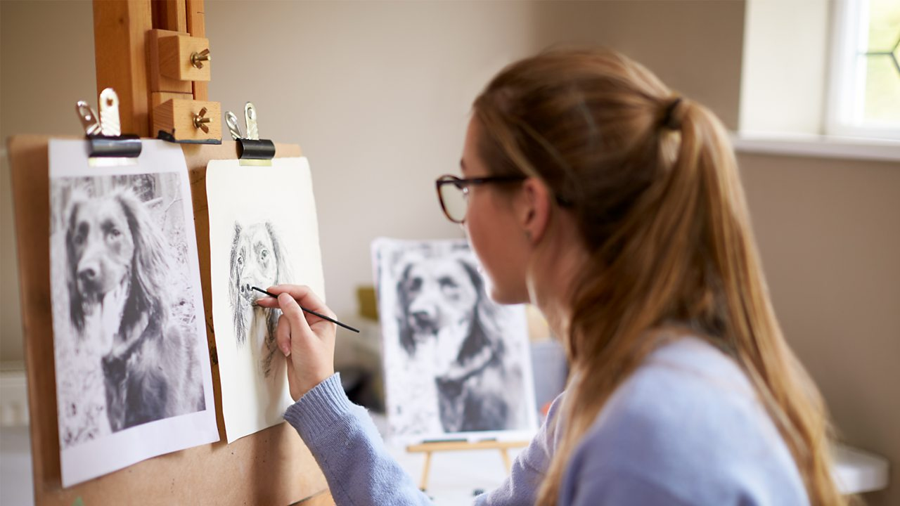 A person draws dog portraits in a bright room against an easel.