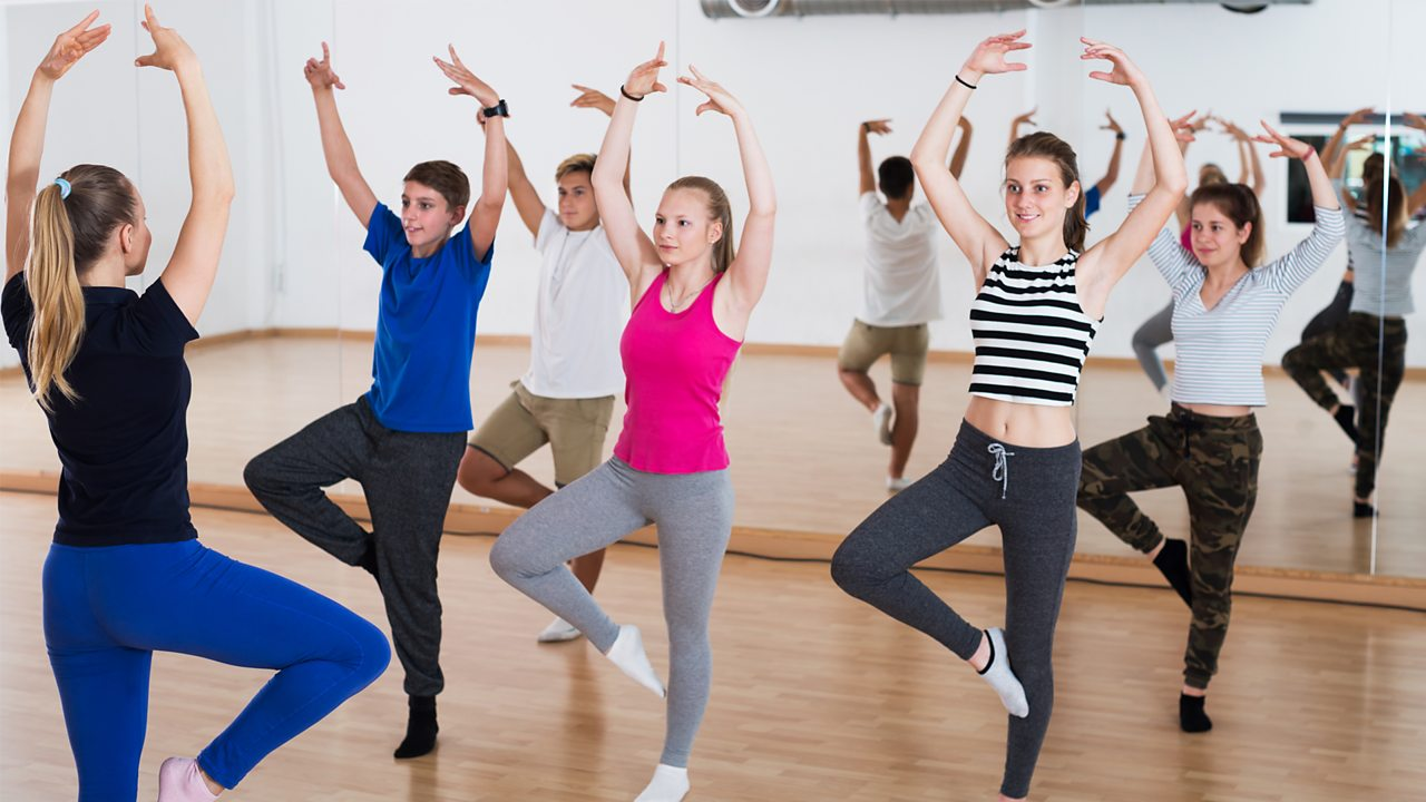 A group of people are dancing in a studio space with their hands in the air, copying the instructor at the front of the class.