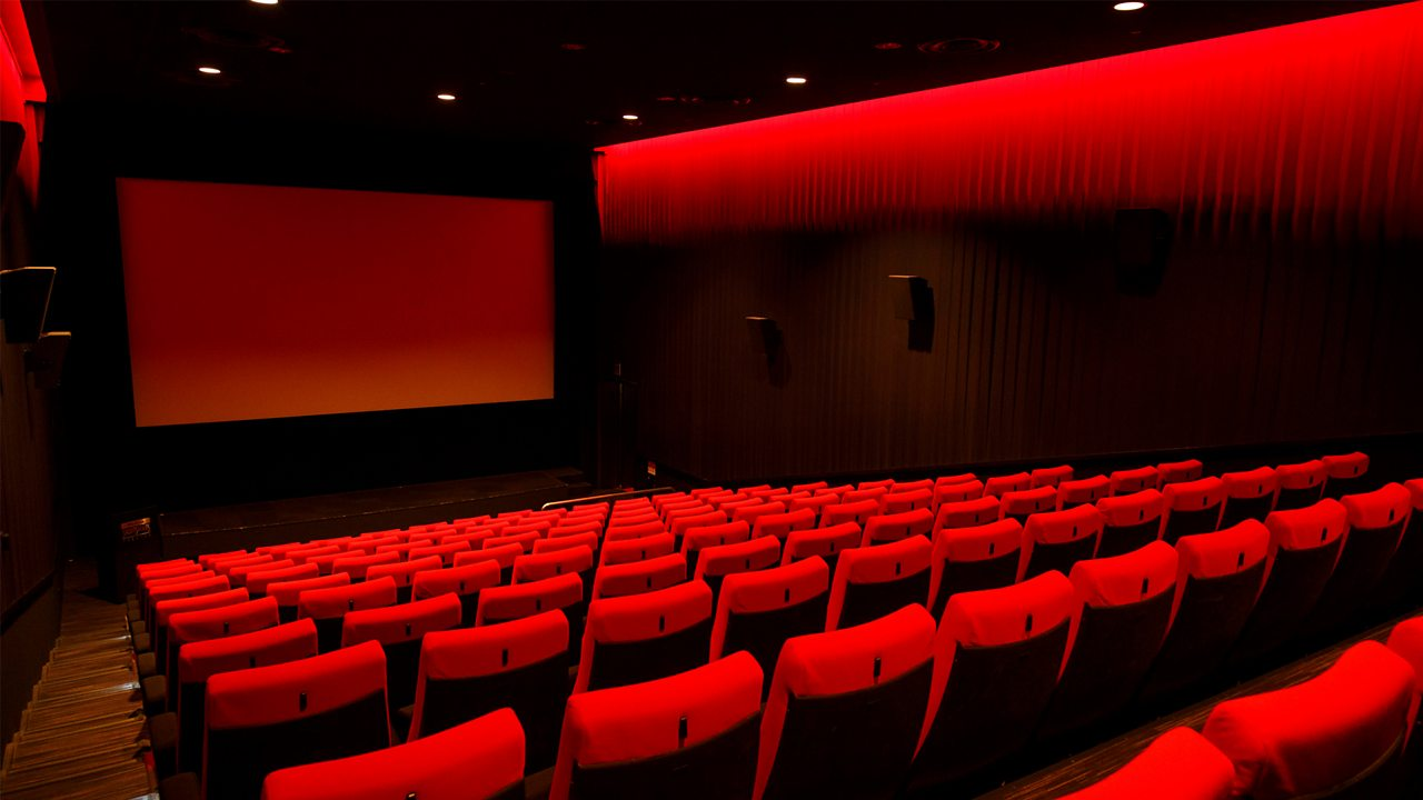 A photo of a cinema screen with rows of red seats.