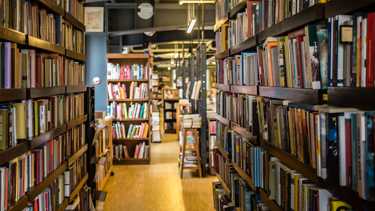 A photo of the inside of a library. There are lots of books on tall shelves.