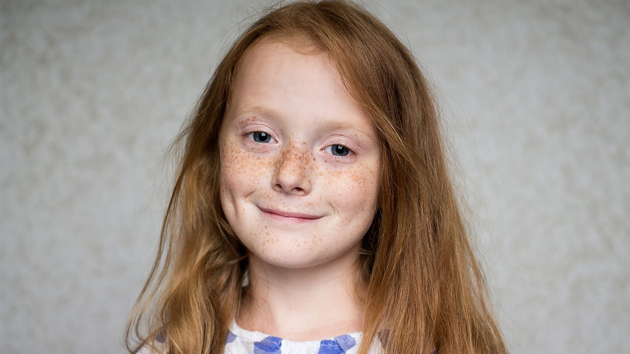A photo of a young girl with freckles
