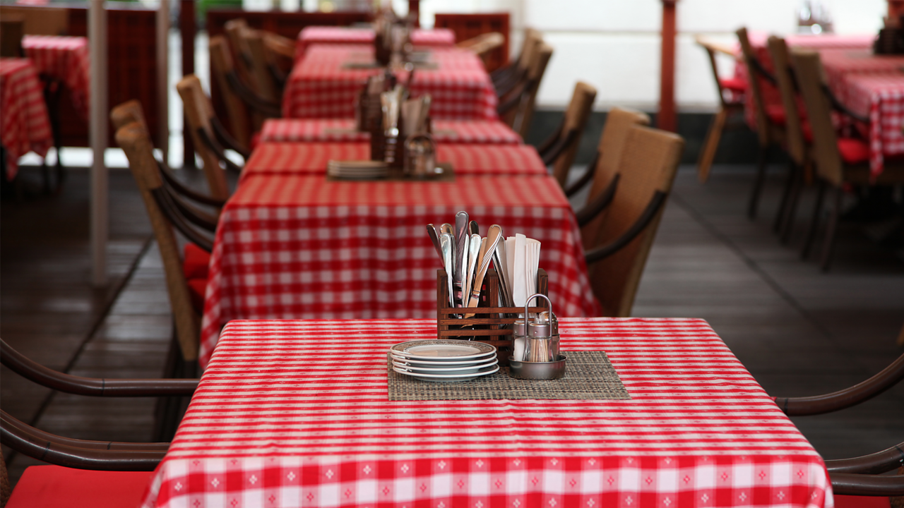 A photo of a table in a restaurant. The table has a red and white table table cloth, four plates, salt, pepper and cutlery.