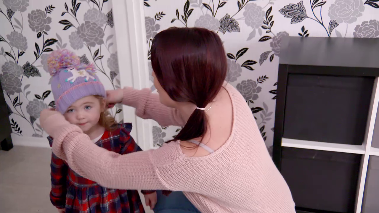 Woman in pink jumper putting purple bobble hat on toddler