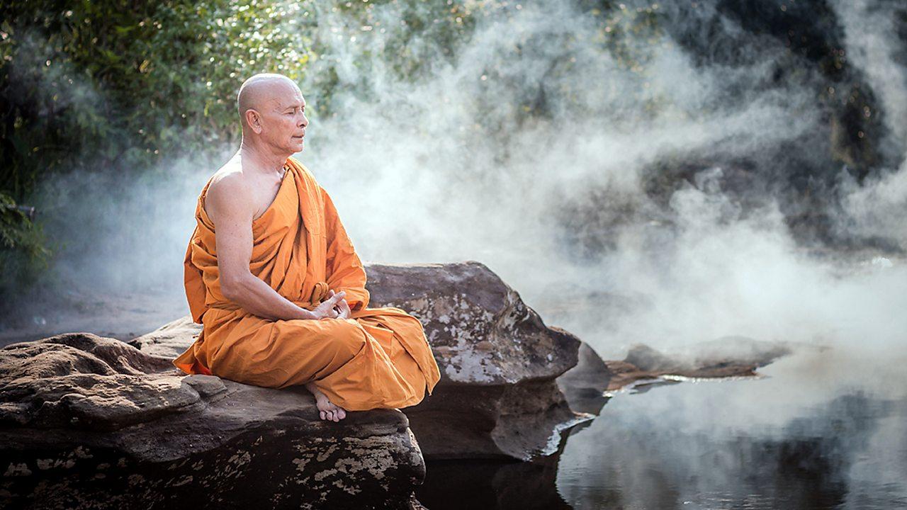 Buddhism – A Buddhist monk meditating outdoors