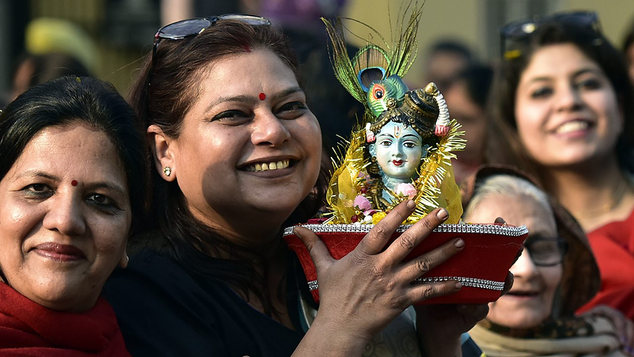 Hinduism – Hindu women with a murti of Lord Krishna
