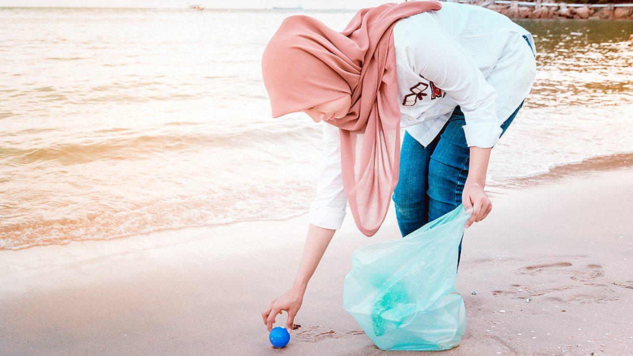 Islam – A Muslim woman cleaning a beach