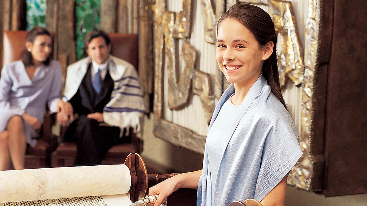 Judaism – A girl reading from the Torah scrolls at her Bat Mitzvah