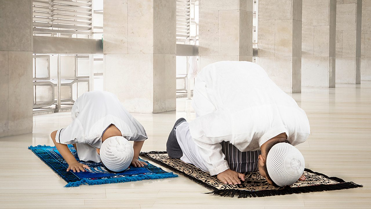 Islam – A father and son pray together at the mosque