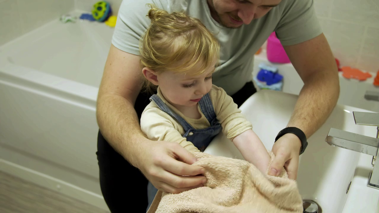 Man sat on side of bath next to sink using towel to dry hands of toddler