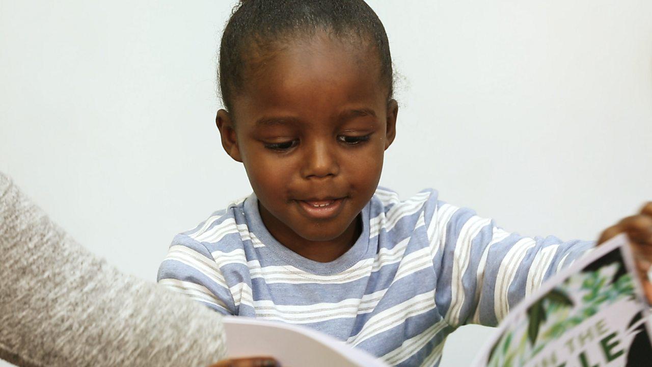 Little boy opening a book.