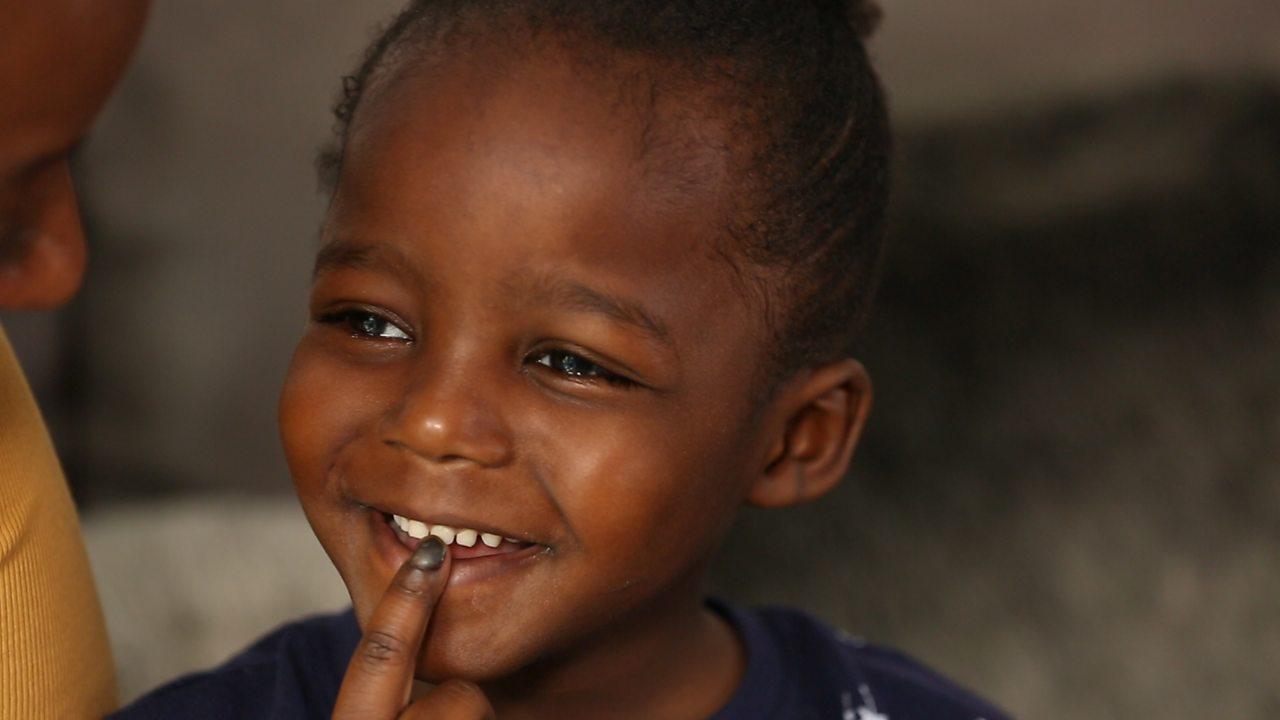 Little boy smiling with a finger on his mouth.