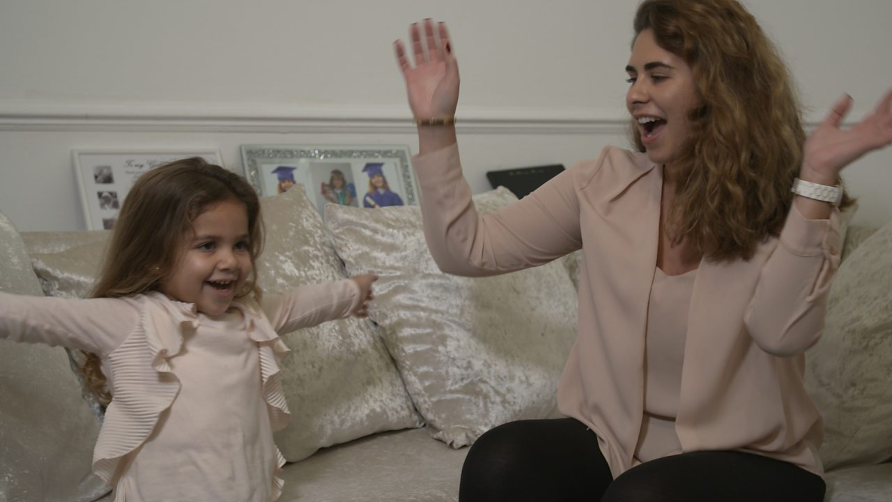 Girl and mum with their arms up.