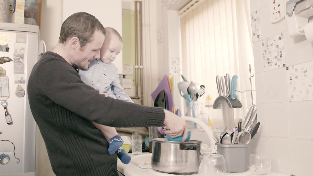 Dad carrying baby whilst washing up dishes.