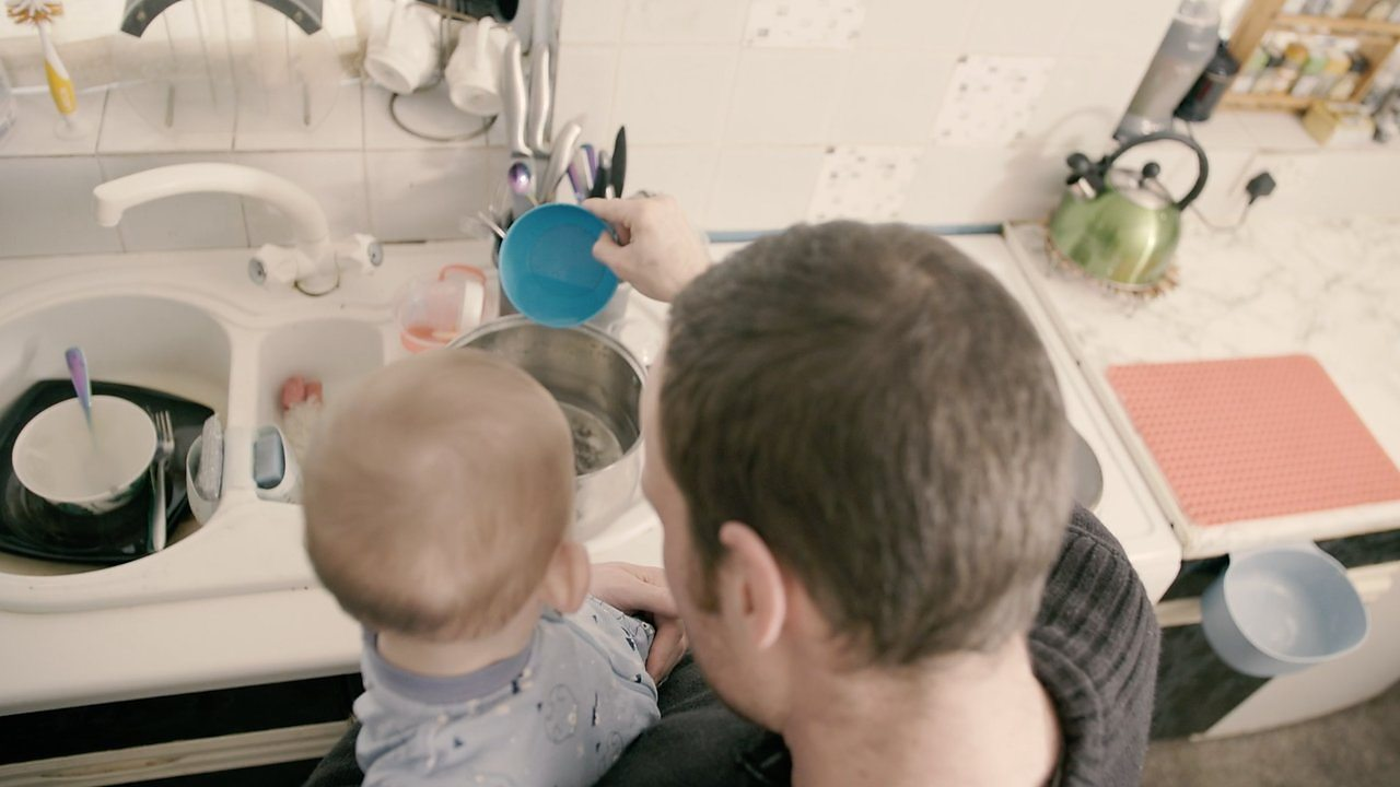 Backs of head of dad and baby over the sink.